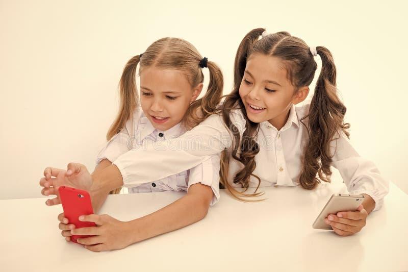 School break for happy little girls using smartphones. little girls using smartphones on school break having fun. stock photo