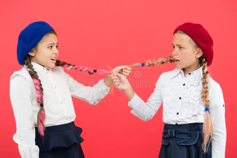 School bullies. Bully girls on pink background. Bully classmates pulling pigtails at school. Bully or bullied stock photos