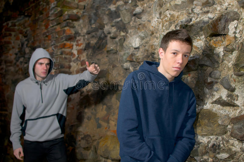 School bully. Angry bully, bullying a young sad boy near a rock wall royalty free stock photos