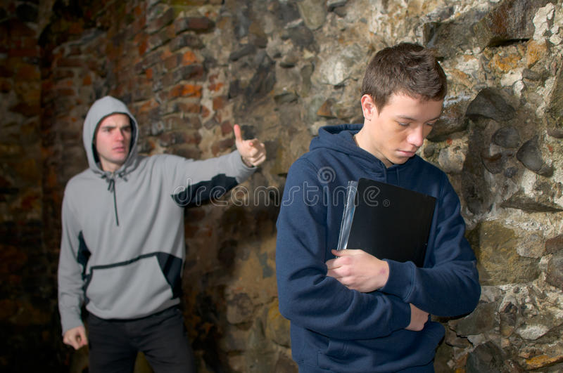 School bully. Angry bully, bullying a young sad boy looking down near a rock wall stock image