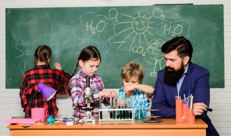 School chemistry experiment. Explaining chemistry to kids. Fascinating chemistry lesson. Man bearded teacher and pupils. With test tubes in classroom. Observe royalty free stock images
