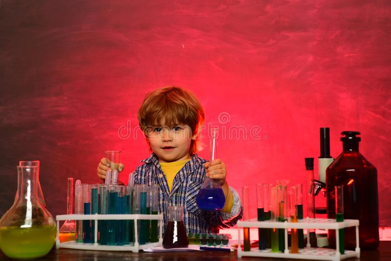 School chemistry lessons. School concept. Child in the class room with blackboard on background. Child from elementary. School. A chemistry demonstration royalty free stock images