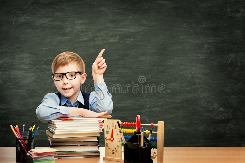 School Child in Classroom over Blackboard Background, Pointing Boy. School Child in Classroom over Blackboard Background, Boy Advertising Pointing Finger to stock photography