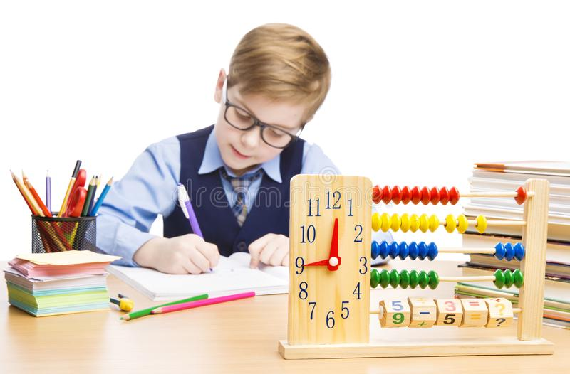 School Child Writing in Classroom, Education Clock and Abacus. On Table, Student Boy Sitting over White Background royalty free stock image