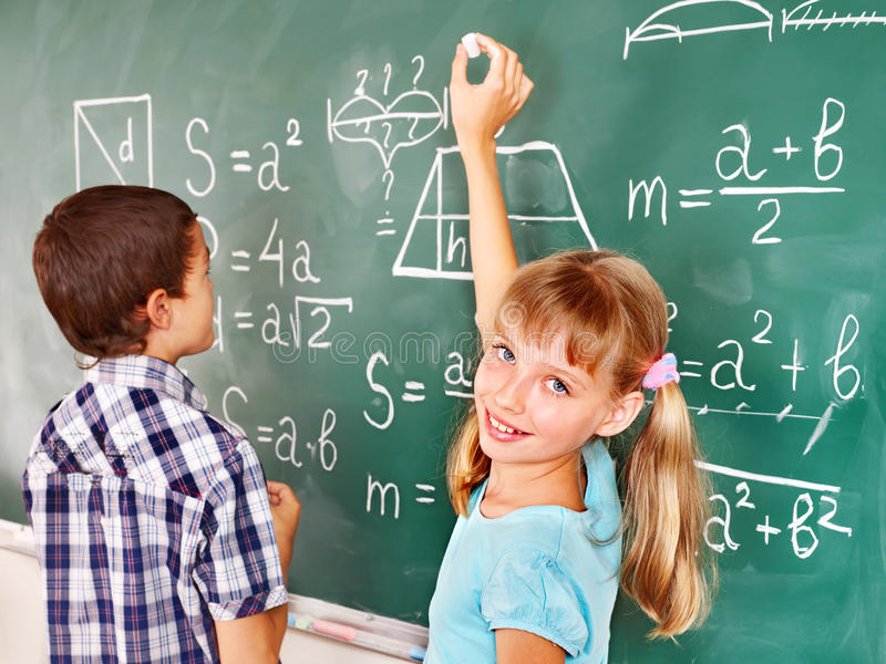 School child writting on blackboard. royalty free stock photo