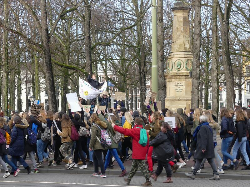 School children at anti climate change protest in The Hague with banners walking through the city royalty free stock photos