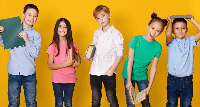 School children with books having fun on background. School children with books having fun on yellow studio background stock photography