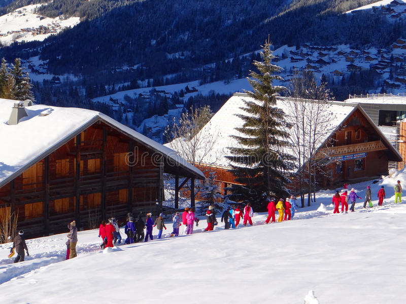 School children in bright colored snowsuits. Walk past traditional ski chalets in Chatel, France in the Alps stock image