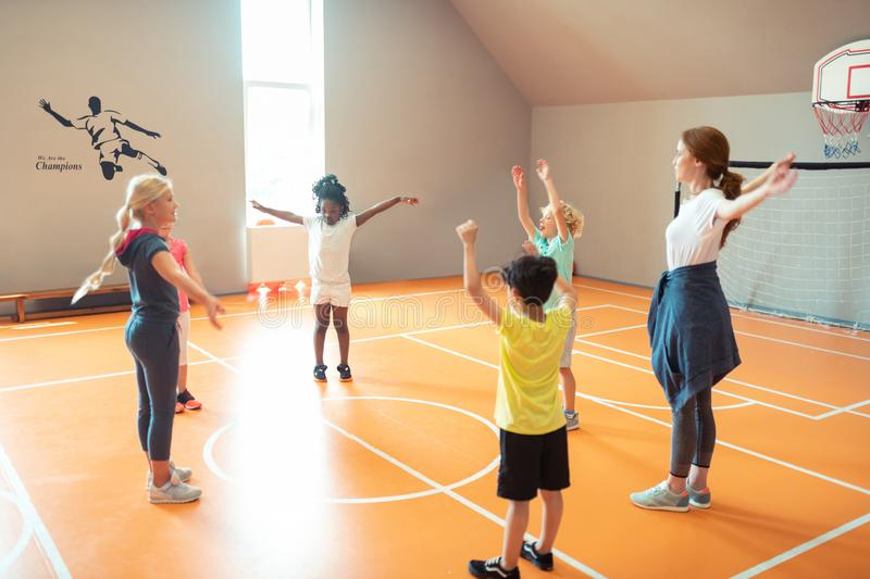 School children exercising during their sports lesson. Physical education. Enthusiastic school children exercising with the teacher during their sports lesson stock photo