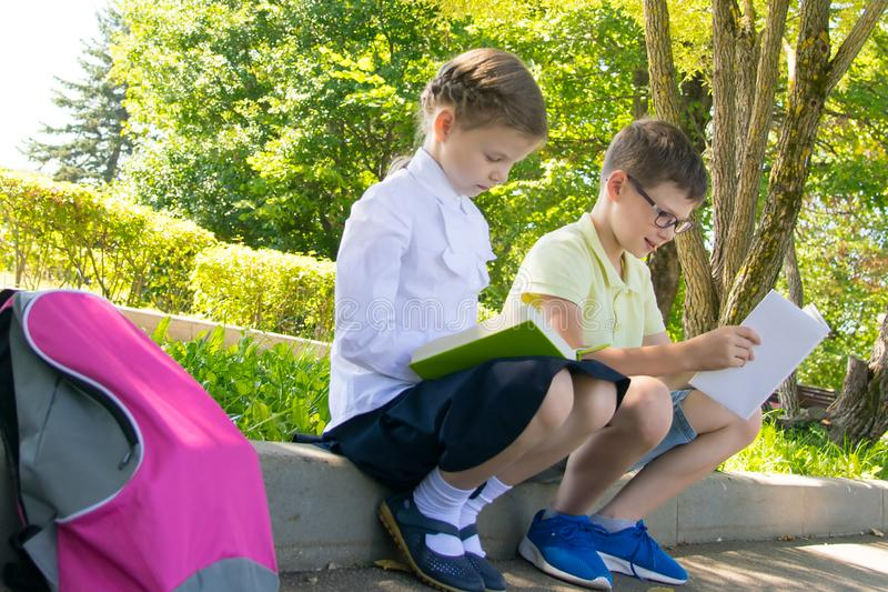 School children outdoors, sit in the park, read books and do homework royalty free stock photos