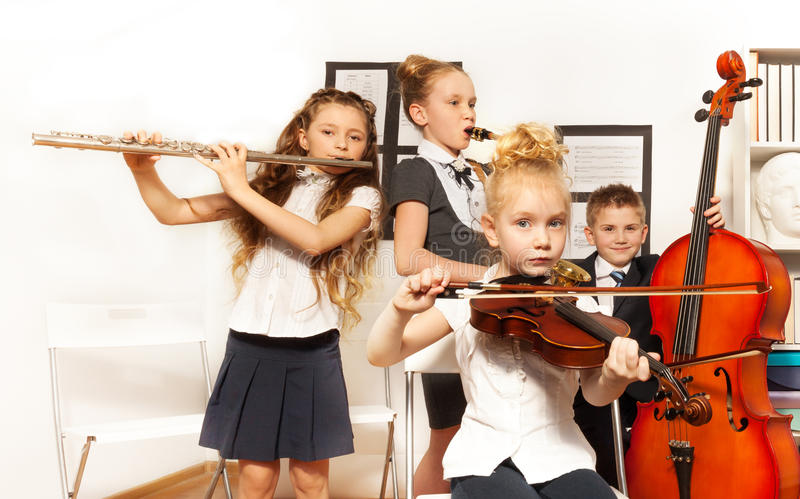 School children play musical instruments together. School children playing musical instruments together during their concert in school royalty free stock images