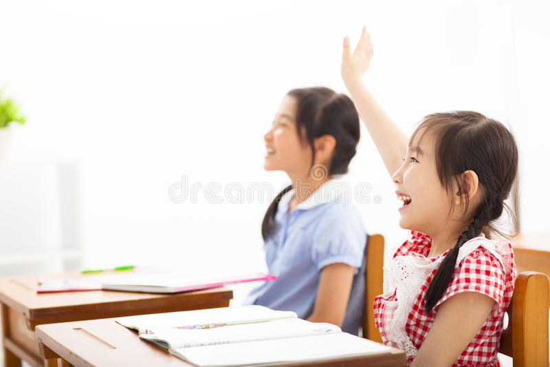 School children raised hands in class stock photography