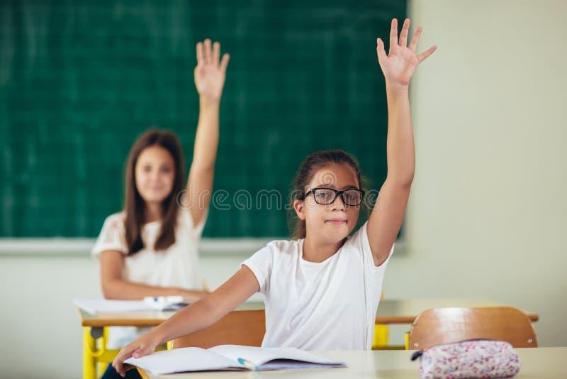 School girls raised hands in class room. School children raised hands in class room stock photography