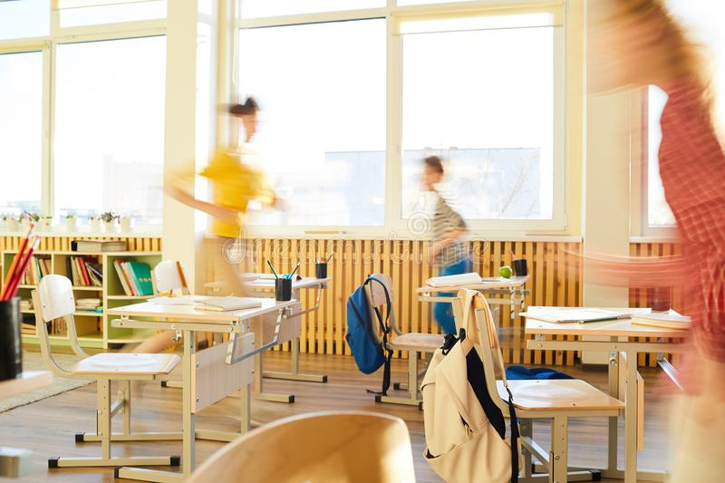 School children running in classroom. Blurred motion of school children running in classroom, school desks and chairs with hanging satchels in classroom royalty free stock photos