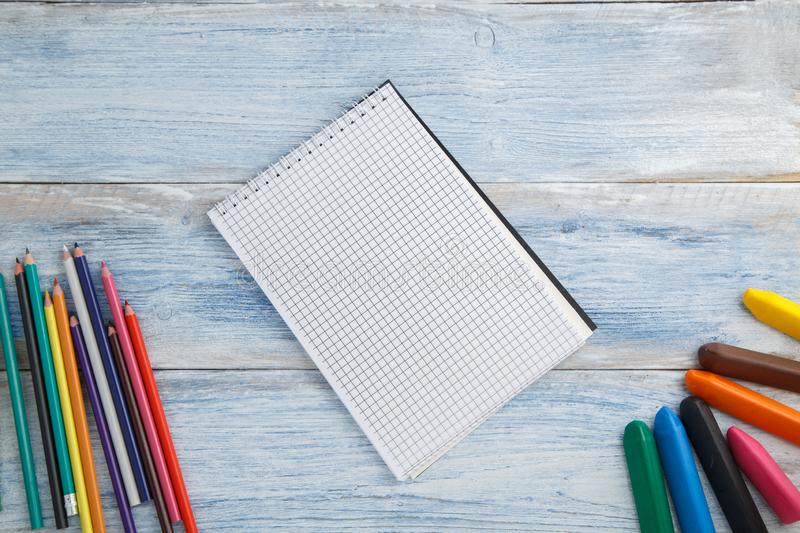 School children`s concept. colored pencils, crayons and Notepad on blue and white scuffed vintage wooden background. the view fro stock photography