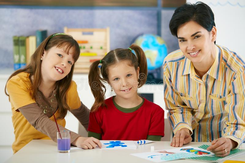 School children and teacher in art class. Portrait of elementary age children and teacher in art class in primary school classroom. Looking at camera, smiling royalty free stock photo