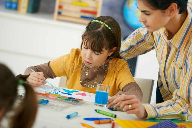 School children and teacher in art class. Teacher teaching painting to elementary age children in classroom at primary school stock images