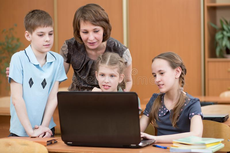 School kids and teacher at laptop in the classroom stock photo