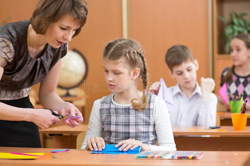 School children working at labour lesson. Teacher looking at pupil. royalty free stock images