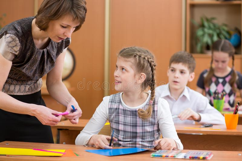 School children working at labour lesson. Teacher looking at pupil. stock images