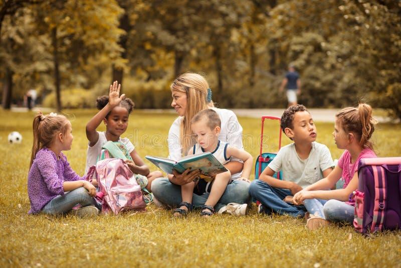 School class at nature. Teacher and children. stock photography
