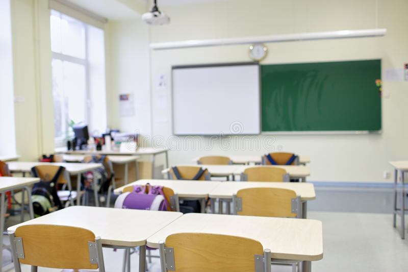 School classroom with desks and blackboard. School, education and learning concept - classroom with desks and blackboard stock photos