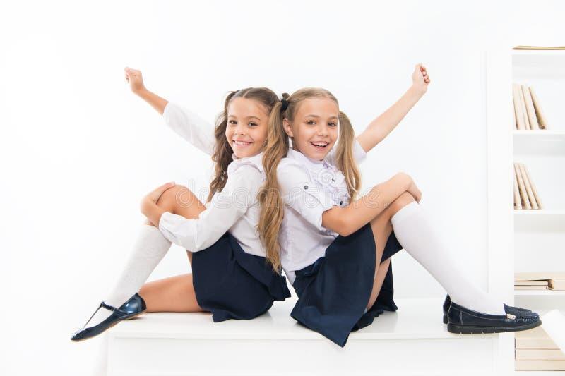 School club. Little schoolgirls classmates friendly kids. Schoolgirls friends sit on desk. Best friends relaxing royalty free stock image