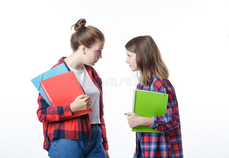School colledge teenagers girl with stationary books notebooks. School colledge teenagers girls with stationary books notebooks are looking at each other arguing royalty free stock photography