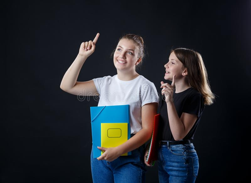 School colledge teenagers girl with stationary books notebooks. School colledge teenagers girls with stationary books notebooks on the dark black background have stock image