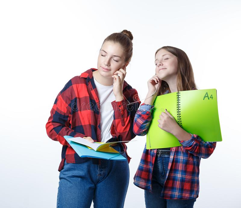 School colledge teenagers girl with stationary books notebooks. School colledge teenagers girls with stationary books notebooks are standing listening to music stock photo