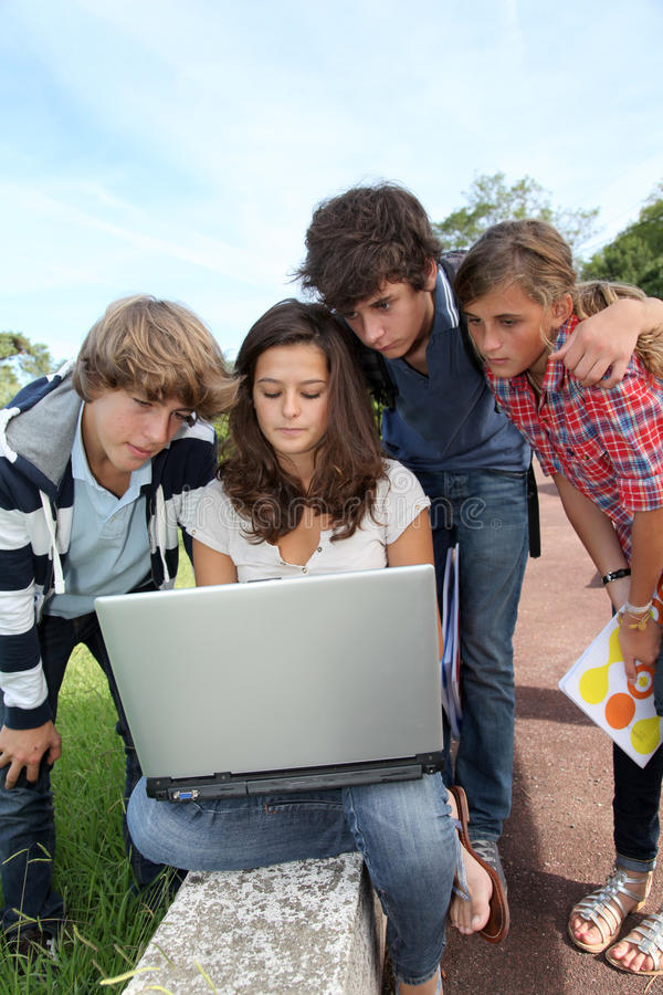 At school with computer. Teenagers sitting outside with laptop computer stock photography