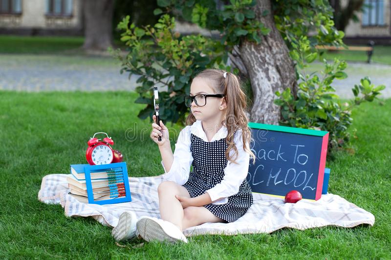 School concept. Back to school. The little girl in glasses holds a magnifying glass magnifier in her hands. Little professor. Ed royalty free stock photo