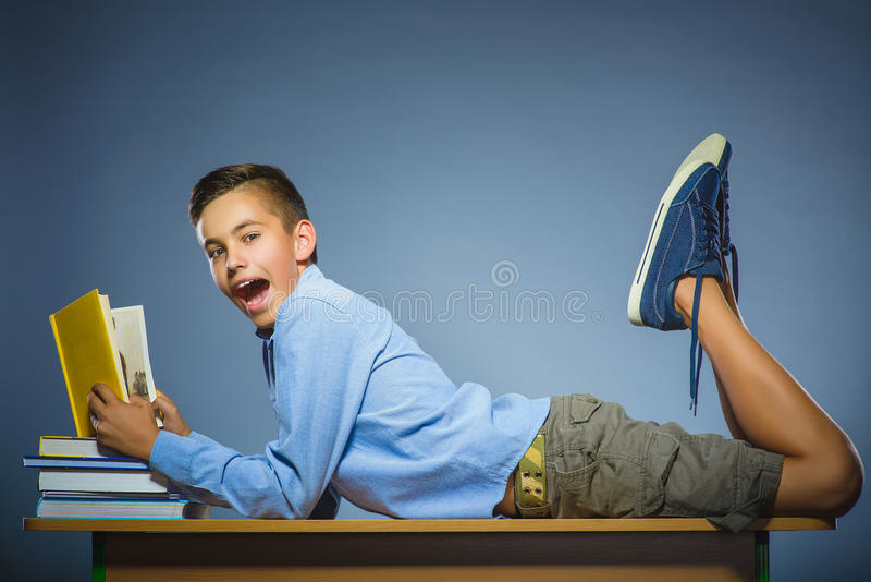 School concept. Boy lying on the desk and reading a book stock images