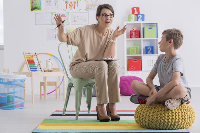 School counselor and pupil. Positive school counselor and pupil sitting in light classroom stock photo