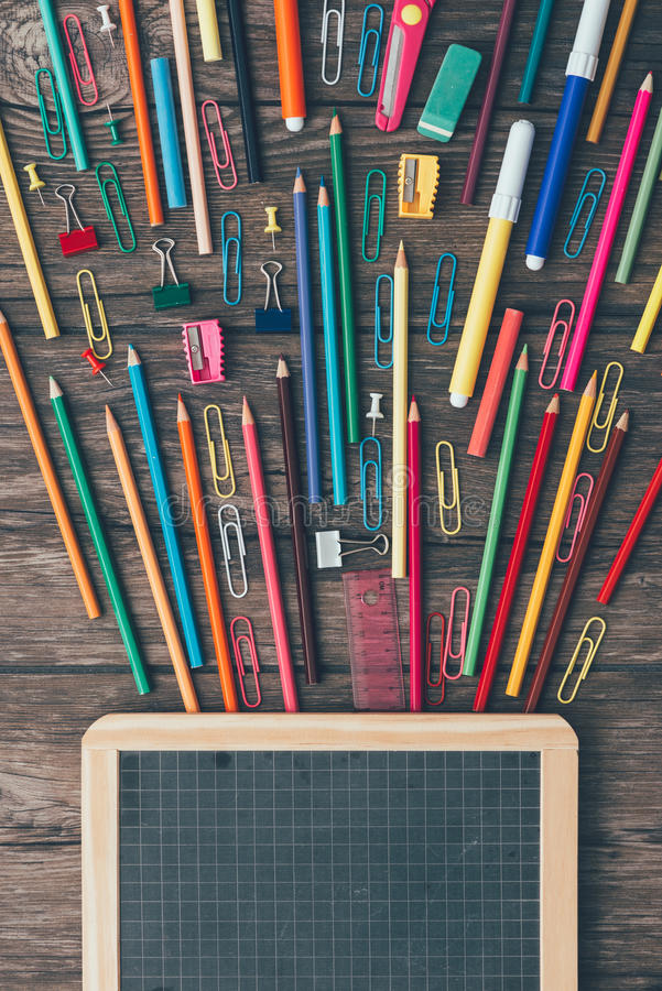 School and creativity. Education, childhood and creativity concept, colorful esplosion of pencils and stationery and vintage blackboard stock images
