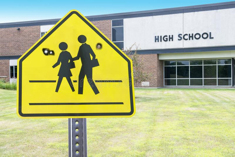 High School Violence, Shooting, Gun. A school crossing sign with bullet holes. Abstract concept for gun violence and shooting. High school building in the stock image