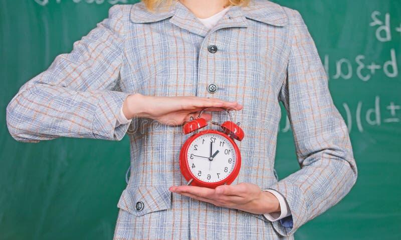 School discipline concept. Schedule and regime. Alarm clock in female hands close up. Teachers attributes. Alarm clock stock photography