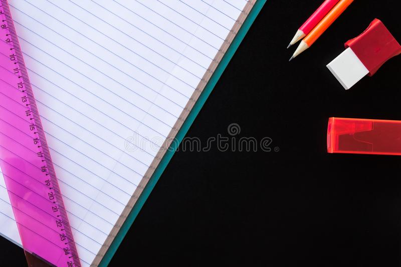 School and drawing supplies, on black background. Exercise book, pencils, eraser, sharpener and ruler. With copy space. stock photo