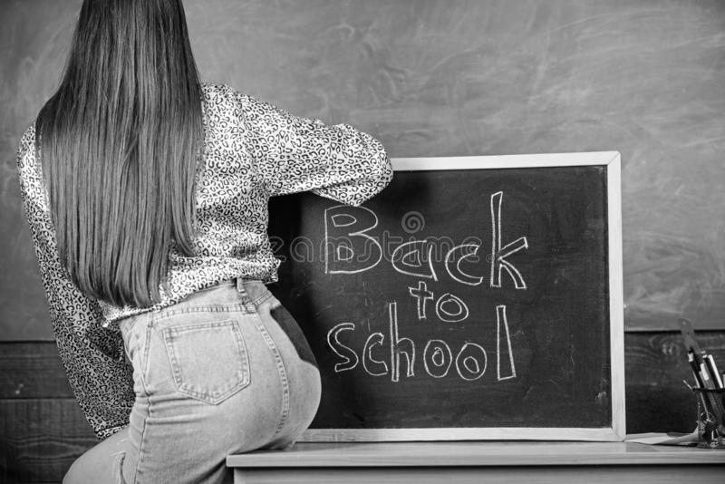 School dress code. Girl denim skirt breaking school clothing rules. Student teacher mini skirt buttocks sit table stock photo