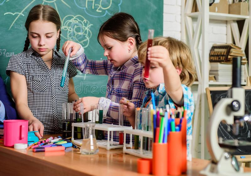 School education. School chemistry experiment. School club. Explaining chemistry to kid. Fascinating chemical reaction. Teacher and pupils with test tubes in stock photography