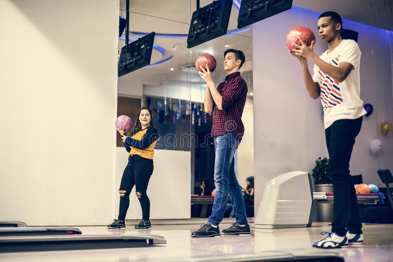 School friends playing bowling together stock photography