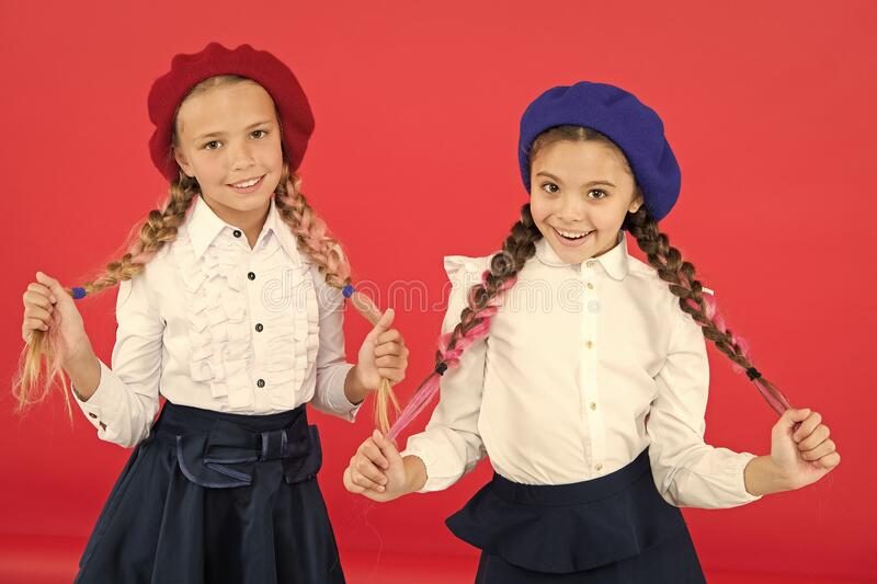 School friendship. On same wave. Schoolgirls wear formal school uniform. Children beautiful girls long braided hair. Fancy style. Little girls with braids stock images