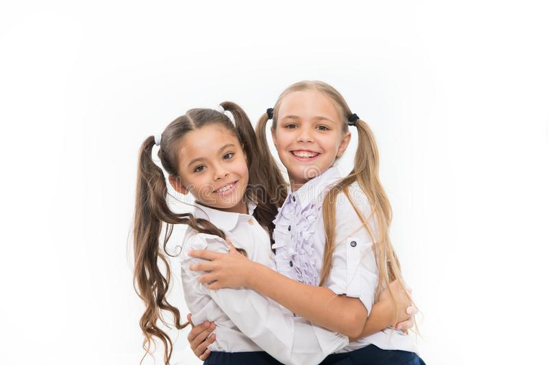 School friendship is so special. Adorable small friends hugging isolated on white. Happy schoolgirls enjoying friendship royalty free stock images