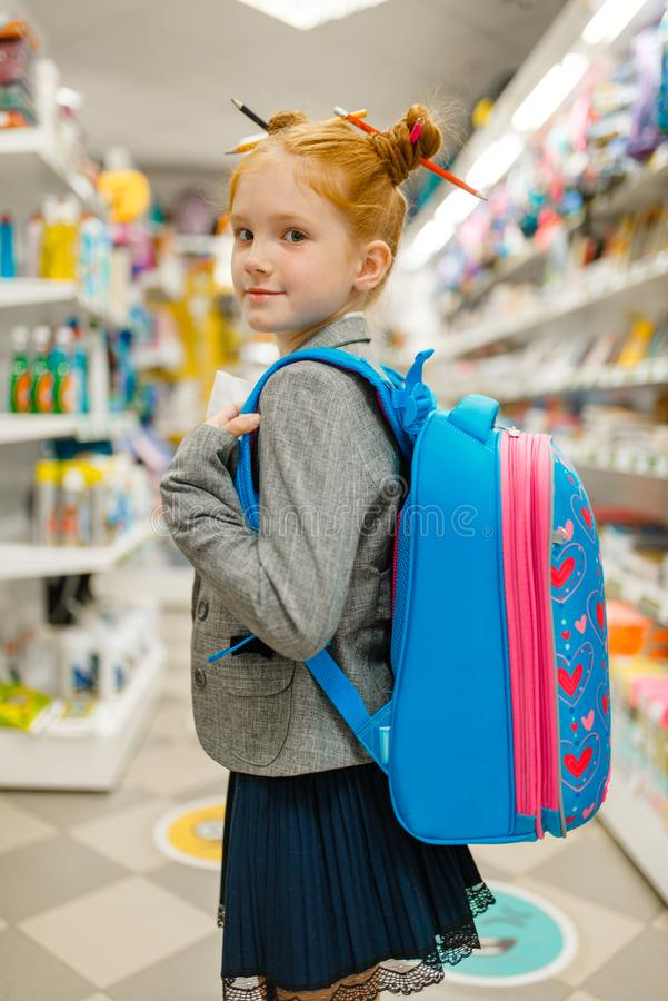 School girl with backpack in stationery store stock photography