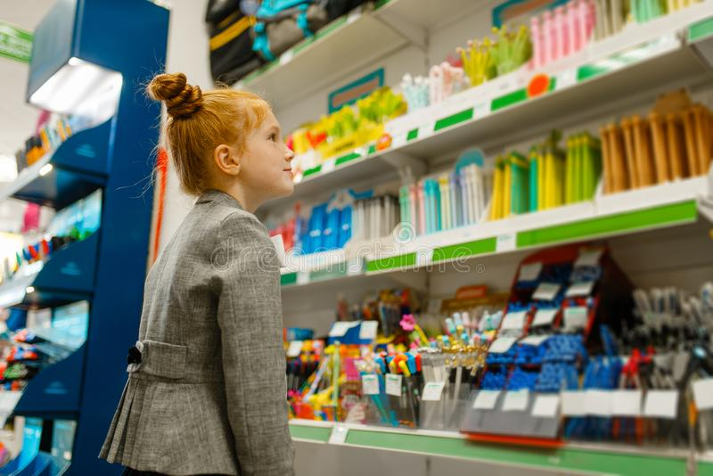 School girl choosing a pencil in stationery store royalty free stock images