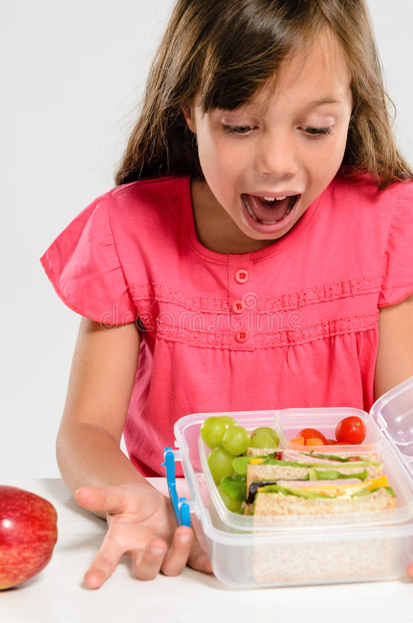 School girl is excited to open her healthy lunch box royalty free stock photo