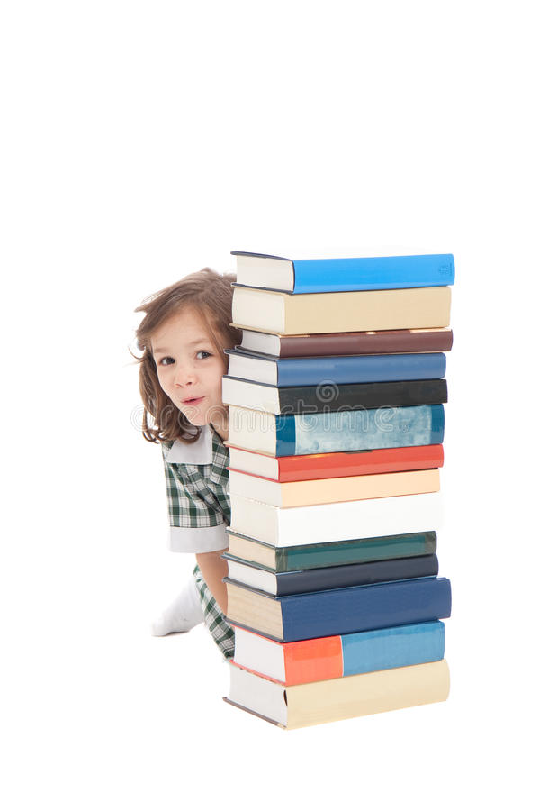 School girl hiding behind books royalty free stock photo