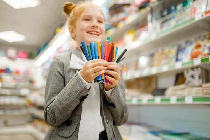 School girl holds markers, stationery store royalty free stock images