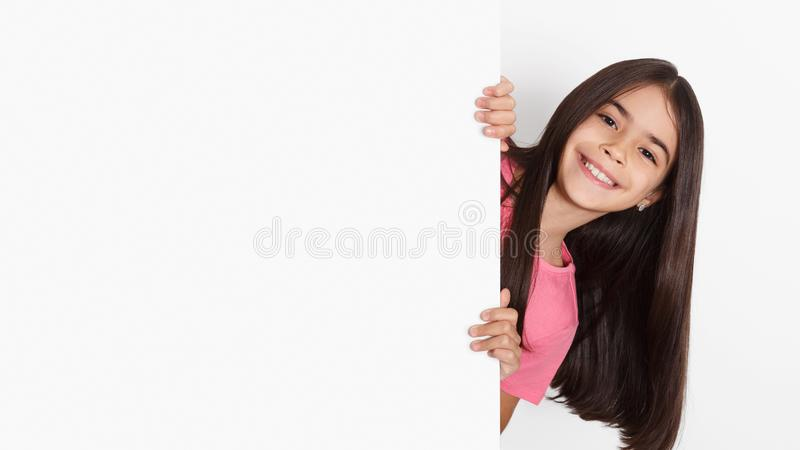 School girl looking behind blank board with copy space stock image