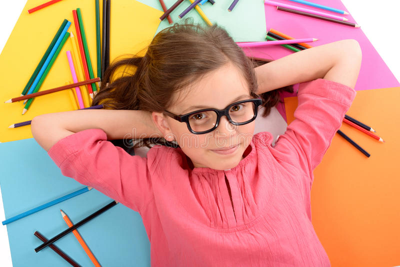 School girl lying on the floor with color pencils stock images